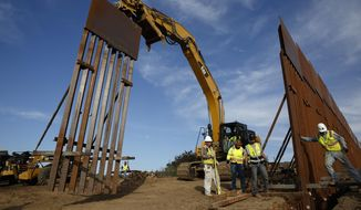 In this Jan. 9, 2019, file photo, construction crews install new border wall sections seen from Tijuana, Mexico. (AP Photo/Gregory Bull, File)
