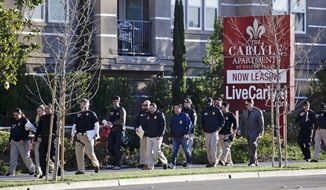 In this March 3, 2015, file photo, federal agents enter an upscale apartment complex where authorities say a birth tourism business charged pregnant women $50,000 for lodging, food and transportation, in Irvine, Calif. On Thursday, Jan. 31, 2019, authorities announced they have charged 20 people in an unprecedented crackdown on businesses that helped hundreds of Chinese women travel to the United States to give birth to American citizen children. (AP Photo/Jae C. Hong, File)