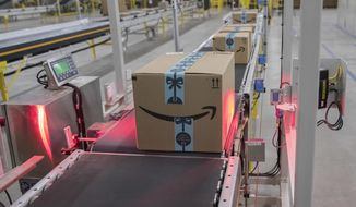 In this Dec. 5, 2018, photo a box is scanned and weighed before at the Amazon fulfillment center on Staten Island borough of New York. Amazon reports financial results Thursday, Jan. 31, 2019. (AP Photo/Mary Altaffer)