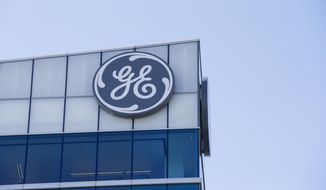 FILE- In this Jan. 16, 2018, file photo the General Electric logo is displayed at the top of their Global Operations Center in the Banks development of downtown Cincinnati. General Electric Co. reports financial results Thursday, Jan. 31, 2019. (AP Photo/John Minchillo, File)