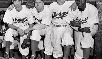 FILE - In this April 15, 1947, file photo, from left, Brooklyn Dodgers baseball players John Jorgensen, Pee Wee Reese, Ed Stanky and Jackie Robinson pose at Ebbets Field in New York. Thursday, Jan. 31, 2017, marked the 100th anniversary of the birth of Jackie Robinson, who broke Major League Baseball's color barrier, on April 15, 1947. AP Photo, File)