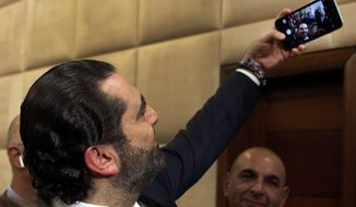 Newly-assigned Lebanese Prime Minister Saad Hariri, takes a selfie with reporters after he announced his new cabinet, at the presidential palace in Baabda, east of Beirut, Lebanon, Thursday, Jan. 31, 2019. Lebanese political factions have agreed on the formation of a new government, breaking a nine-month deadlock that only deepened the country' economic woes. (AP Photo/Hussein Malla)