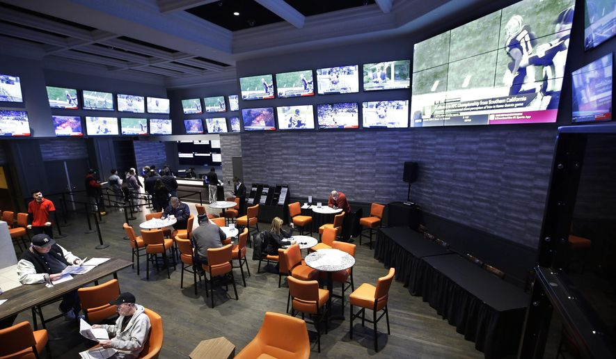 In this Monday, Jan. 28, 2019 photo, patrons visit the sports betting area of Twin River Casino in Lincoln, R.I. New England Patriots fans are gearing up for Super Bowl 53 by betting on the team to win over the Los Angeles Rams, the first time they can do so legally in New England. Rhode Island is the only state in the region that has launched sports betting so far. (AP Photo/Steven Senne) **FILE**