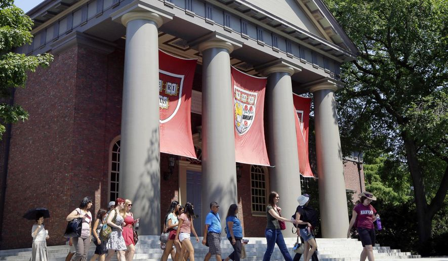 In this Aug. 30, 2012, file photo, a tour group walks through the campus of Harvard University in Cambridge, Mass. (AP Photo/Elise Amendola, File)