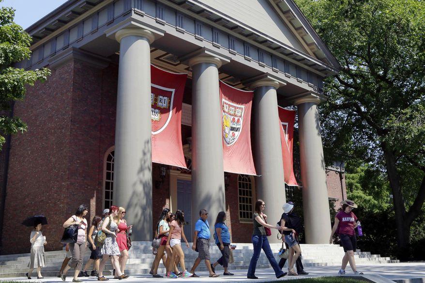In this Aug. 30, 2012, file photo, a tour group walks through the campus of Harvard University in Cambridge, Mass. (AP Photo/Elise Amendola, File)