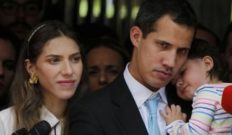 """Opposition National Assembly President Juan Guaido, accompanied by his wife Fabiana Rosales and his 20-month-old daughter Miranda, listens to a reporter's question during a news conference outside their apartment, in Caracas, Venezuela, Thursday, Jan. 31, 2019. Guaido said security forces showed up at their home in an attempt to intimidate him. """"The dictatorship thinks it can intimidate us,"""" Guaido said. (AP Photo/Fernando Llano)"""