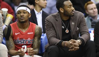 Washington Wizards guard John Wall, right, watches from the bench next to guard Bradley Beal (3) during the second half of an NBA basketball game against the Indiana Pacers, Wednesday, Jan. 30, 2019, in Washington. The Wizards won 107-89. (AP Photo/Nick Wass) ** FILE **