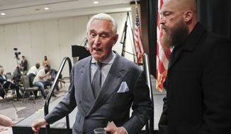 Roger Stone, center, longtime friend and confidant of President Donald Trump, walks next to a member of his private hired security, right, as he walks off stage after speaking to members of the media in Washington, Thursday, Jan. 31, 2019. (AP Photo/Pablo Martinez Monsivais)