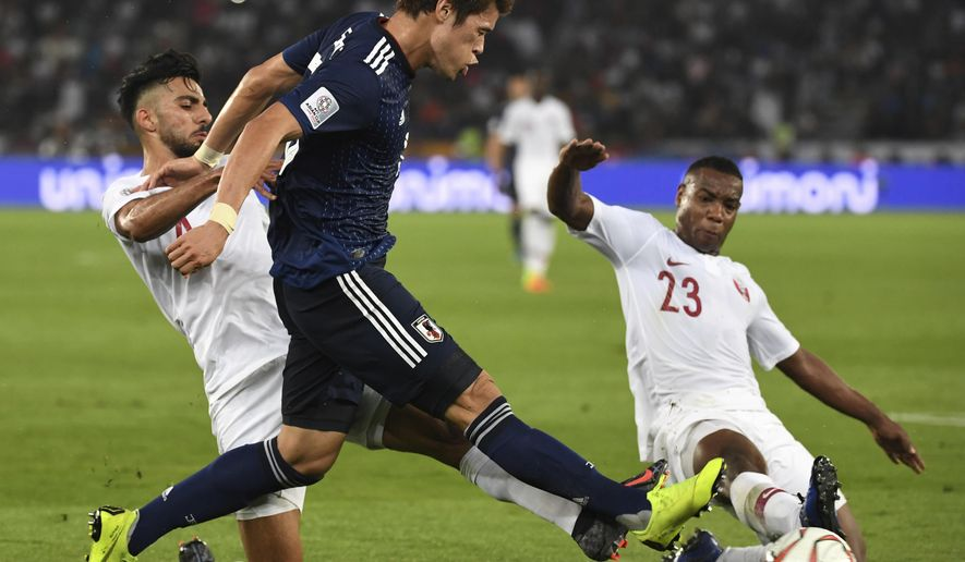Qatar's defender Tarek Salman, left, and Qatar's defender Assim Madibo, right, challenge Japan's defender Hiroki Sakai, center, during the AFC Asian Cup final match between Japan and Qatar in Zayed Sport City in Abu Dhabi, United Arab Emirates, Friday, Feb. 1, 2019. (AP Photo/Hassan Ammar)