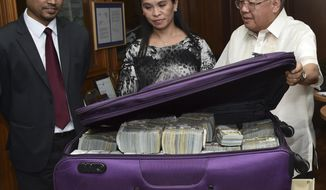 FILE - In this March 31, 2016, file photo provided by the Bangko Sentral ng Pilipinas, from left; Second Secretary of the Bangladesh Embassy in Manila Probash Lamarong, Anti-Money Laundering Council (AMLC) Director Julia Bacay-Abad and AMLC Member Emmanuel Dooc opens a case containing US dollars that was returned by Chinese casino junket operator Kam Sin Wong to Bangladesh and Philippine AMLC officials in Manila, Philippines. Bangladesh's central bank has filed a lawsuit in the U.S. District Court for the Southern District of New York against Philippine private bank over the heist of $81 million from Bangladesh Bank's account with the Federal Reserve Bank of New York. The head of Bangladesh Bank's Finance Intelligence Unit confirmed the lawsuit against the Rizal Commercial Banking Corp. (Jason Arlan Raval/Bangko Sentral ng Pilipinas via AP)