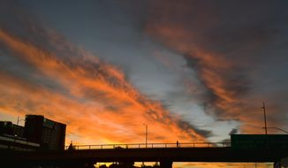 A pedestrian makes their way across an overpass under a dramatic sunrise during the early morning commute in Los Angeles on Friday, Feb. 1, 2019. A powerful storm heading toward California is expected to produce heavy rainfall, damaging winds, localized stream flooding and heavy snow in the Sierra Nevada. Forecasters say rain will arrive in the north late Friday afternoon and reach the south late in the night, and last through Saturday night. (AP Photo/Richard Vogel)