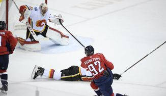 Washington Capitals center Evgeny Kuznetsov (92), of Russia, scores a goal past Calgary Flames goaltender Mike Smith (41) during the third period of an NHL hockey game Friday, Feb. 1, 2019, in Washington. (AP Photo/Nick Wass)