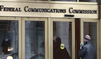 "FILE - In this Thursday, Dec. 14, 2017, file photo, a person with a smartphone enters the Federal Communications Commission building in Washington. Tech companies and nearly two dozen U.S. states clashed with the government in federal court Friday, Feb. 1, 2019, over the repeal of net neutrality, a set of Obama-era rules aimed at preventing big internet providers from discriminating against certain technology and services. The action rolling back the neutrality rules ""is a stab in the heart of the Communications Act,"" said attorney Pantelis Michalopoulos, referring to the Depression-era law that established the FCC. (AP Photo/Carolyn Kaster, File)"