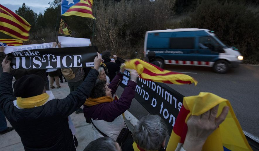 Demonstrators hold esteladas, or independence flags, as they gather in support of the imprisoned Catalan politicians outside the Brians II prison, in Barcelona, Spain, Friday, Feb.1, 2019. Authorities are transferring nine politicians and activists from prisons in Catalonia to the country's capital, Madrid, ahead of a high-stakes trial for their role in an attempt to break Spain's territorial unity. (AP Photo/Emilio Morenatti)