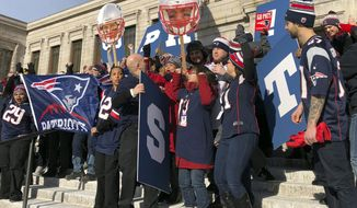 Workers at Boston's Museum of Fine Arts rally outside in New England Patriots garb on Friday, Feb. 1, 2019 in Boston. The museum and Los Angeles' J. Paul Getty Museum are trading a little trash talk ahead of the Super Bowl between the Patriots and the Rams. (AP Photo/Bill Kole)