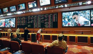 FILE - In this May 14, 2018, file photo, people make bets in the sports book at the South Point hotel and casino in Las Vegas. Las Vegas is not worried about the competition from casinos in other states that for the first time Sunday, Feb. 3, 2019, will also offer football fans a chance to bet on the Super Bowl. The weekend is worth hundreds of millions of dollars to the city, which draws tens of thousands of people for the big game's weekend. (AP Photo/John Locher, File)