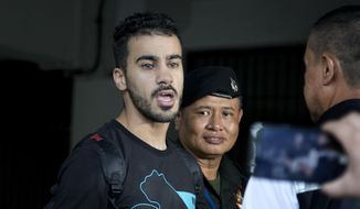 FILE - In this Tuesday, Dec. 11, 2018, file photo. Bahraini football player Hakeem al-Araibi answers questions from the waiting journalists as he is brought in to a court in Bangkok, Thailand. Thai prosecutors have submitted a request in court for Thailand to extradite to Bahrain a detained soccer player who has refugee status in Australia. (AP Photo/Gemunu Amarasinghe, File)