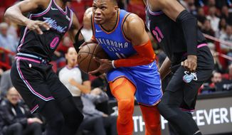 Oklahoma City Thunder guard Russell Westbrook, center, drives to the basket against Miami Heat guard Josh Richardson (0) and center Hassan Whiteside (21) during the first half of an NBA basketball game, Friday, Feb. 1, 2019, in Miami. (AP Photo/Wilfredo Lee)