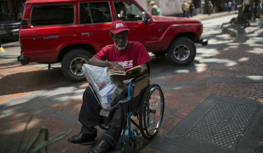 Raul Sanz, a supporter of Venezuela's President Nicolas Maduro, reads a book on his wheelchair in downtown in Caracas, Venezuela, Friday, Feb.1, 2019. Momentum is growing for Venezuela's opposition movement led by lawmaker Juan Guaido, who has called supporters back into the streets for nationwide protests Saturday, escalating pressure on embattled President Nicolas Maduro to step down. (AP Photo/Rodrigo Abd)