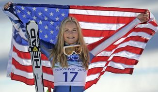 FILE -In this Feb. 20, 2010 file photo, bronze medalist Lindsey Vonn of the United States hold the Stars and Stripes during the flower ceremony for the Women's super-G at the Vancouver 2010 Olympics in Whistler, British Columbia. Vonn announced Friday, Feb. 1, 2019, that she will retire from ski racing after this month's world championships in Sweden. (AP Photo/Gero Breloer, File)