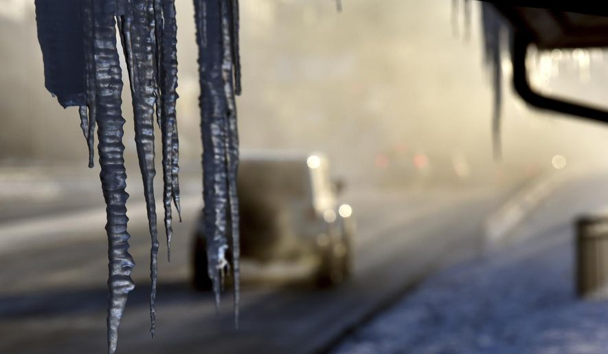 Icicles hang from the Harrington Inn in Geneva, Ill., as commuters pass by on Thursday, Jan. 31, 2019. The cold weather system holding much of the Midwest in a historic deep freeze sent temperatures plunging to a record low in northern Illinois on Thursday. (Jeff Knox/Daily Herald via AP)