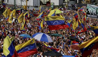 Anti-government protesters wave Venezuelan national flags as they take part in a demonstration demanding the resignation of President Nicolas Maduro, in Caracas, Venezuela, Saturday, Feb. 2, 2019. Momentum is growing for Venezuela's opposition movement led by self-declared interim president Juan Guaido, who has called supporters back into the streets for nationwide protests Saturday, escalating pressure on Maduro to step down. (AP Photo/Fernando Llano)