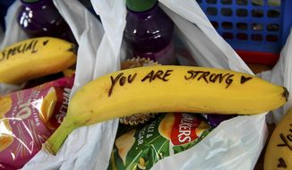 In this Friday, Feb. 1, 2019 photo, messages written on bananas by Meghan, the Duchess of Sussex as she helped to prepare food parcels to be dispatched by the charity outreach van, during her visit with Britain's Prince Harry to One25, a charity specialising in helping women to break free from street sex work, addiction and other life-controlling issues.  (Toby Melville/Pool Photo via AP)