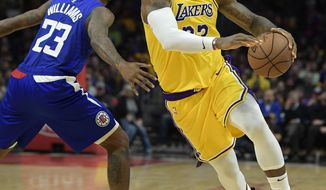 Los Angeles Lakers forward LeBron James, right, drives by Los Angeles Clippers guard Lou Williams during the second half of an NBA basketball game Thursday, Jan. 31, 2019, in Los Angeles. The Lakers won 123-120. (AP Photo/Mark J. Terrill)