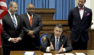 FILE - In this June 5, 2017, file photo, then Nevada Republican Gov. Brian Sandoval talks to reporters before signing a series of budget bills while flanked by legislative leaders in the Old Assembly Chambers at the state Capitol in Carson City, Nev. From left, Assembly Minority Leader Paul Anderson, R-Las Vegas; Assembly Speaker Jason Frierson, D-Las Vegas; and Senate Majority Leader Aaron Ford, D-Las Vegas. Nevada Democrats say they will likely take a pass on overriding more than a dozen bills vetoed by former Gov. Sandoval following the last legislative session. Instead, Democratic lawmakers expect to reintroduce similar bills on criminal justice and other topics, allowing its many new members to weigh in on the issues for the new session. (AP Photo/Scott Sonner, File)
