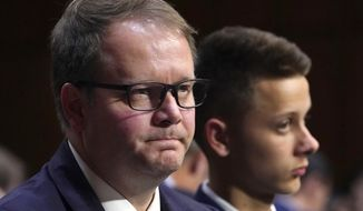 FILE - In this March 14, 2018 file photo, Ryan Petty, left, waits to testify as he sits next to his son Patrick Petty, at a Senate Judiciary Committee hearing on the Parkland, Fla., school shootings and school safety on Capitol Hill in Washington.  Petty and Andrew Pollack, two parents who lost daughters in last year's school shooting are calling for their local newspaper to win the Pulitzer Prize.  They say the South Florida Sun Sentinel has stayed on the story to demand accountability long after the national media left.  (AP Photo/Jacquelyn Martin, File)
