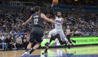 Orlando Magic guard D.J. Augustin (14) passes the ball while defended by Brooklyn Nets forward Joe Harris (12) during the first half of an NBA basketball game in Orlando, Fla., Saturday, Feb. 2, 2019. (AP Photo/Willie J. Allen Jr.)
