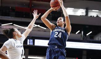 Connecticut's Napheesa Collier (24) shoots over Cincinnati's Angel Rizor (4) in the first half of an NCAA college basketball game, Saturday, Feb. 2, 2019, in Cincinnati. (AP Photo/John Minchillo)