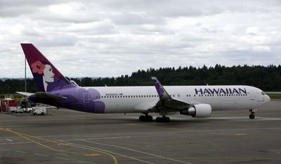FILE - In this June 7, 2010 file photo an Hawaiian Airlines plane is shown at Seattle-Tacoma International Airport in Seattle. American Airlines is dropping money-losing flights between Chicago and Shanghai, and Hawaiian Airlines will suspend its only route to China because of low demand. (AP Photo/Ted S. Warren, File)