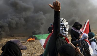 A masked protester chants while others burn tires and waving their national flags near the fence of Gaza Strip border with Israel during a protest east of Gaza City, Friday, Nov. 9, 2018. Gaza's Hamas rulers said Friday that deadly protests along Gaza-Israel perimeter fence have achieved some goals; $15 million from Qatar to help pay the salaries of civil servants. (AP Photo/Adel Hana)