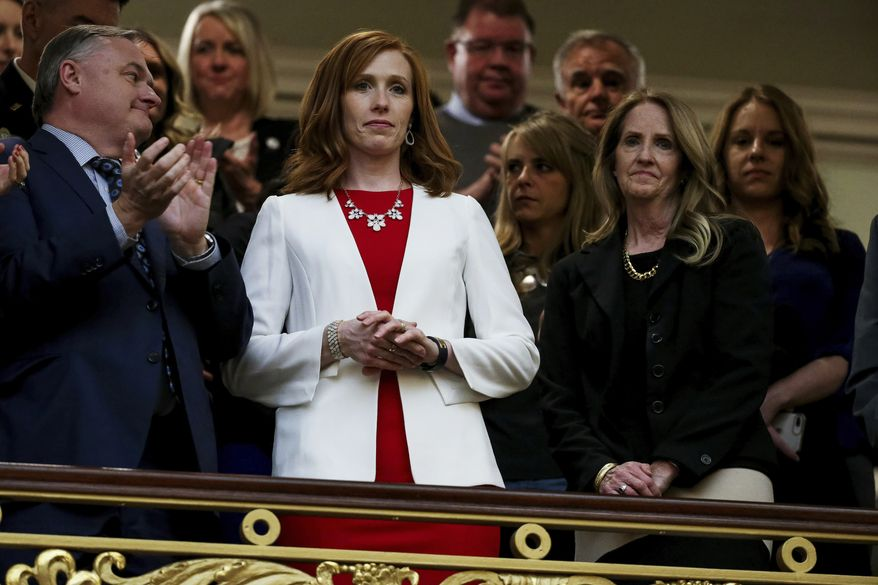 Jennie Taylor, center, wife of slain Utah National Guard Maj. Brent Taylor, and Tammy Taylor, Maj. Taylor's mother, stand as the House chamber audience rises to honor the families of Utahns who fell in the line of duty in the last year during Utah Gov. Gary Herbert's State of the State address at the Utah State Capitol Wednesday, Jan. 30, 2019, in Salt Lake City. (Spenser Heaps/Deseret News, via AP, Pool)