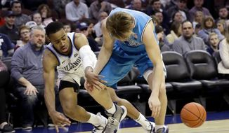 Villanova's Phil Booth, left, knocks the ball loose from Georgetown's Mac McClung during the second half of an NCAA college basketball game, Sunday, Feb. 3, 2019, in Philadelphia. (AP Photo/Matt Slocum)