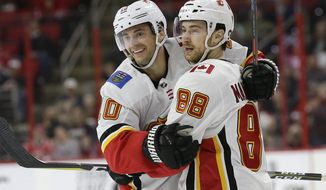 Calgary Flames' Derek Ryan (10) is congratulated by Andrew Mangiapane (88) after his goal against the Carolina Hurricanes during the second period of an NHL hockey game in Raleigh, N.C., Sunday, Feb. 3, 2019. (AP Photo/Gerry Broome)