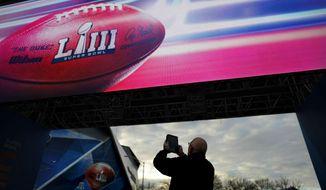 Frank Egdmann, of Kiel, Germany, takes a photo of Mercedes-Benz Stadium ahead of Sunday's NFL Super Bowl 53 football game between the Los Angeles Rams and New England Patriots in Atlanta, Saturday, Feb. 2, 2019. (AP Photo/David Goldman)