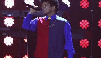 "FILE - In this Feb. 22, 2017 file photo, singer Bruno Mars performs on stage at the Brit Awards 2017 in London. Mars may have wrapped up his massive ""24K Magic World Tour"" last year, but the singer gave one more glimpse into his stellar show the night before the Super Bowl. Some concertgoers danced down the aisles, others threw their hands up high and the majority recited Mars' lyrics at the Bud Light Super Bowl Music Fest on Saturday night, Feb. 2, 2019, in Atlanta. (Photo by Joel Ryan/Invision/AP, file)"