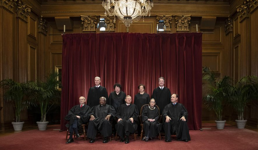 In this Nov. 30, 2018, file photo the justices of the U.S. Supreme Court gather for a formal group portrait to include a new Associate Justice, top row, far right, at the Supreme Court Building in Washington. (AP Photo/J. Scott Applewhite, File) **FILE**