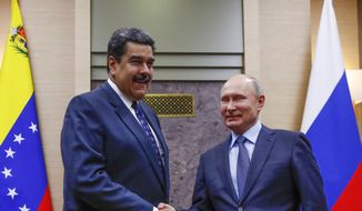 Russian President Vladimir Putin, right, shakes hands with his Venezuelan counterpart Nicolas Maduro during their meeting at the Novo-Ogaryovo residence outside in Moscow, Russia, Wednesday, Dec. 5, 2018. (Maxim Shemetov/Pool Photo via AP) ** FILE **