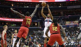 Washington Wizards guard Bradley Beal (3) shoots against Atlanta Hawks center Dewayne Dedmon (14) and forward Taurean Prince (12) during the second half of an NBA basketball game, Monday, Feb. 4, 2019, in Washington.  (AP Photo/Nick Wass)