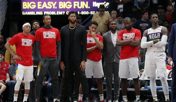 New Orleans Pelicans forward Anthony Davis, center in street clothes, watches form the bench with teammates late in the second half of an NBA basketball game in New Orleans, Monday, Feb. 4, 2019. The Pacers won 109-107. (AP Photo/Gerald Herbert)