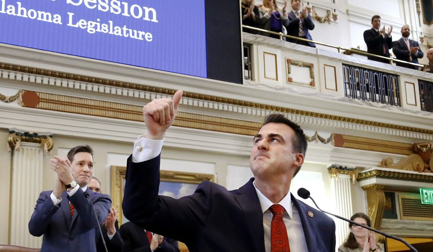 Oklahoma Gov. Kevin Stitt waves to friends and family members in the gallery as he is welcomed into the House chamber to deliver his first State of the State message to a joint session of the Legislature at the Capitol on Monday, Feb. 4, 2019, in Oklahoma City. (Jim Beckel/The Oklahoman via AP) ** FILE **