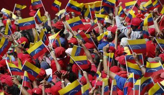 Supporters of President Nicolas Maduro wave Venezuelan national flags during a rally in Caracas, Venezuela, Saturday, Feb. 2, 2019. Maduro called the rally to celebrate the 20th anniversary of the late President Hugo Chavez's rise to power. (AP Photo/Ariana Cubillos)