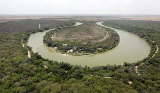 FILE - In this July 24, 2014, file photo, a bend in the Rio Grand is viewed from a Texas Department of Public Safety helicopter on patrol over in Mission, Texas. The U.S. government is preparing to begin construction of more border walls and fencing in South Texas' Rio Grande Valley, likely on federally-owned land set aside as wildlife refuge property. Heavy construction equipment is supposed to arrive starting Monday. A photo posted by the nonprofit National Butterfly Center shows an excavator parked on its property. (AP Photo/Eric Gay, Pool, File)