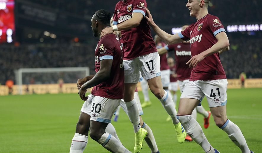 West Ham's Michail Antonio, left, celebrates with West Ham's Chicharito, centre, and West Ham's Declan Rice after scoring his side's first goal during the English Premier League soccer match between West Ham United and Liverpool at the London Stadium in London, Monday, Feb. 4, 2019.(AP Photo/Kirsty Wigglesworth)