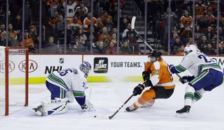 Philadelphia Flyers' Jakub Voracek (93) scores a goal against Vancouver Canucks' Jacob Markstrom (25) as Alexander Edler (23) defends during the second period of an NHL hockey game, Monday, Feb. 4, 2019, in Philadelphia. (AP Photo/Matt Slocum)
