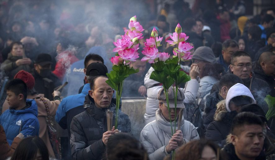 People hold floral bouquets and sticks of incense as they pray at the Lama Temple in Beijing, Tuesday, Feb. 5, 2019. Chinese people are celebrating the first day of the Lunar New Year on Tuesday, the Year of the Pig on the Chinese zodiac. (AP Photo/Mark Schiefelbein)