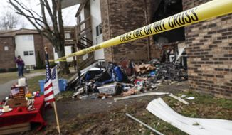 Police tape surrounds an apartment damaged by fire involved in a shooting incident that resulted in the death of a Clermont County Sheriff's Office Deputy, Monday, Feb. 4, 2019, in Pierce Township, Ohio. Suspect Wade Edward Winn was charged with aggravated murder and attempted aggravated murder. (AP Photo/John Minchillo)